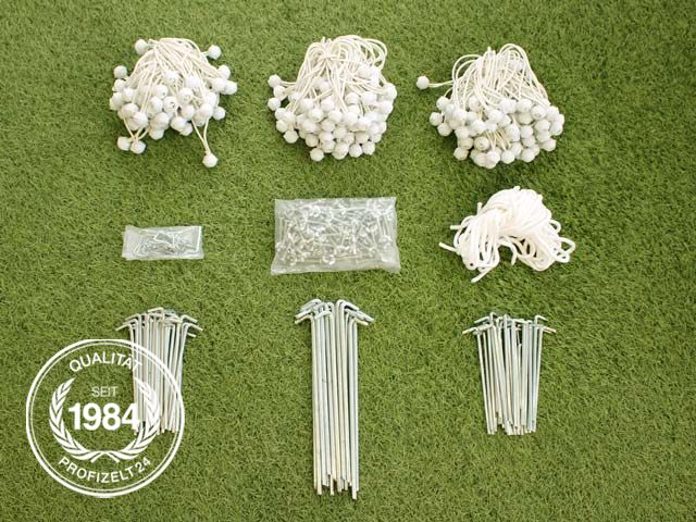 Gummischlaufen, Abspannseile, Erdnägel und weitere Teile auf Rasenfläche gelegt