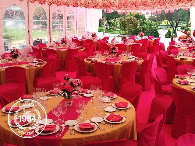 Dekoriertes Partyzelt mit runden Tischen und Stühlen.