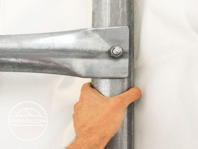 Zwei Personen hängen mit den Handen an der Stahl-Konstruktion