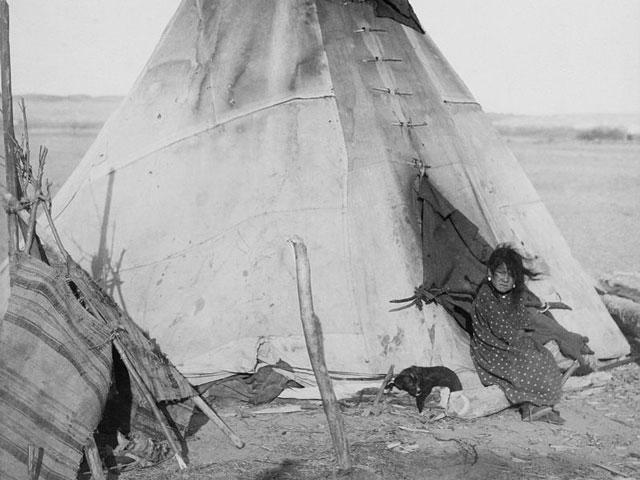 Eine Indianerin betritt ein Tipi.