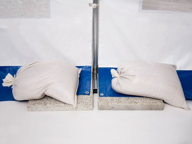 Sandsäcke beschweren und fixieren das Zeltgestänge und die Zeltplane