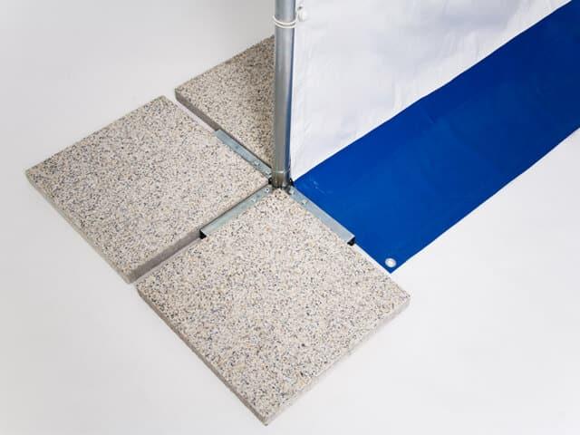 Das Zeltfußset wird mit Betonplatten beschwert